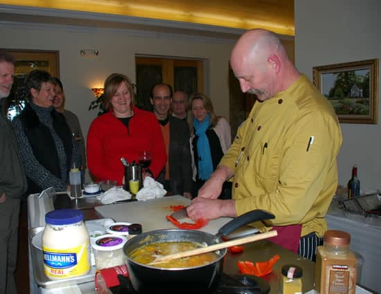 People surrounding a kitchen station with a chef preparing a meal