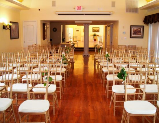 Large room with hardwood flooring set up for a wedding ceremony