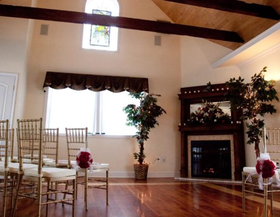 Large room with hardwood flooring and fireplace in the corner set up for a wedding ceremony