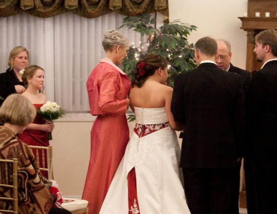 Bride in white dress with red accents and groom in black suit standing at the alter