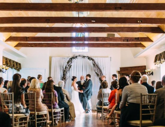Large room with hardwood flooring and bride in white dress and groom in gray suit standing at the alter