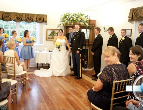 Large room with hardwood flooring, bride in white dress and groom in military uniform standing at the front, and people sitting for the ceremony