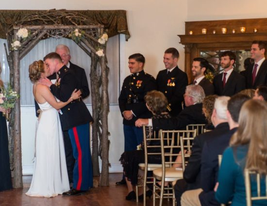 Bride in white dress and groom in military uniform kissing at the alter