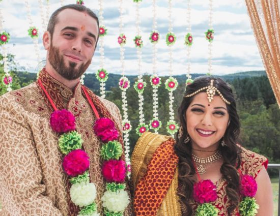 Bride and groom dressed in traditional Indian wedding attire with white, green, and pink flower leis
