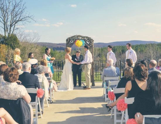 Patio set up for wedding ceremony with bridal party in teal dresses, bride in white dress, and groom and groomsmen in white shirts and khaki pants
