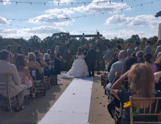 Patio set up for wedding ceremony with father giving away the bride in a white dress