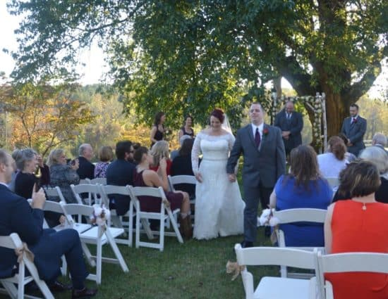 Wedding ceremony outside near large tree with bride in white dress and groom in gray suit walking down the aisle