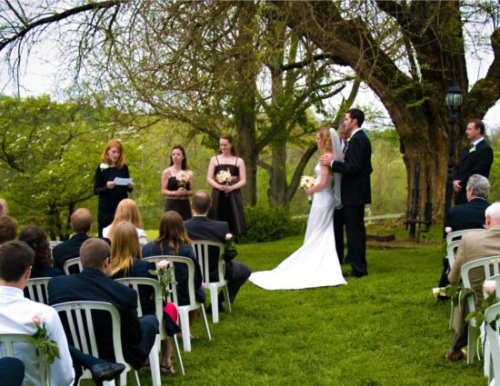 Wedding ceremony outside near large tree with bride in white dress and groom in black suit