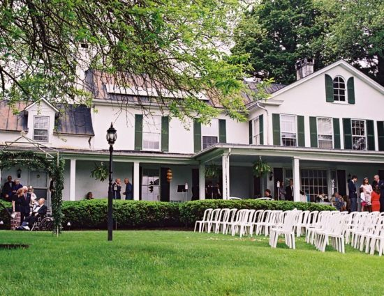 Exterior view of main house painted white with green shutters with lawn set up for wedding ceremony with white chairs