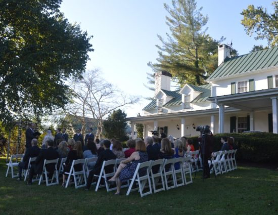 Wedding ceremony outside near large tree and front of house with bride in white dress and groom in gray suit