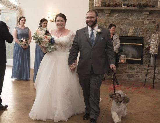 Large room with concrete flooring, bride in white dress, groom in gray suit, and dog walking down the aisle