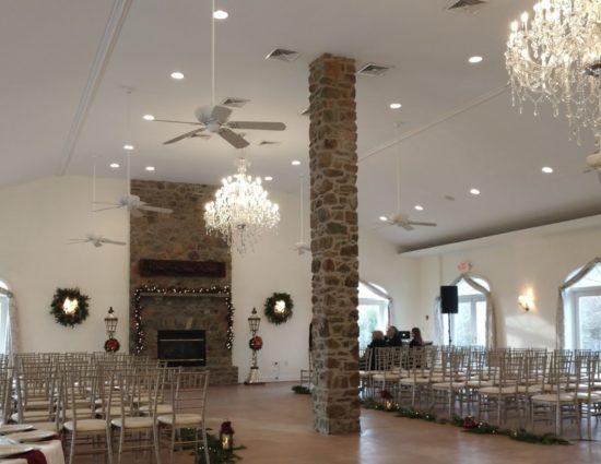 Large room with concrete flooring set up for wedding ceremony