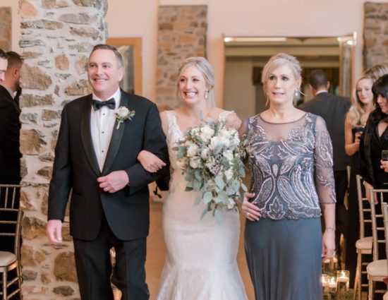 Bride in white dress with father in black suit and mother in gray dress walking bride down the aisle