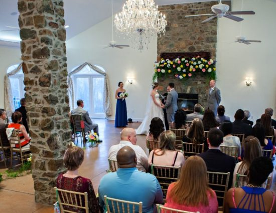 Large room with concrete flooring set up for a wedding ceremony with the maid of honor in a blue dress and best man in a gray suit