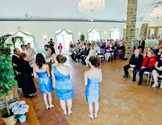 Large room with concrete flooring set up for a wedding ceremony with the wedding party in blue dresses and light tan suits