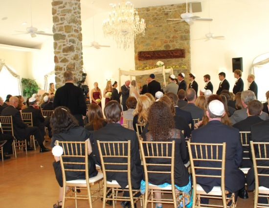 Large room with concrete flooring set up for a wedding ceremony with the wedding party in burgundy dresses and black suits