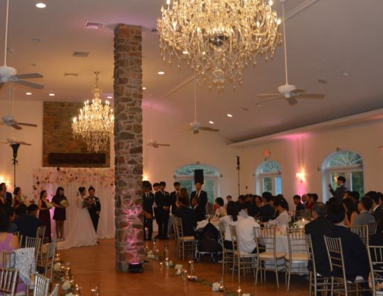 Large room with concrete flooring, bride in white dress and groom in black suit standing at the alter, and people sitting at tables watching the ceremony