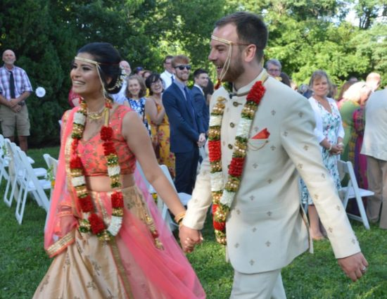 Bride and groom in traditional Indian wedding attire walking down aisle together holding hands