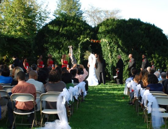 Wedding ceremony near large green shrubs with bride in white dress and groom in black suit