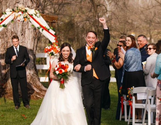 Bride with white dress and groom with black suit walking down the aisle together