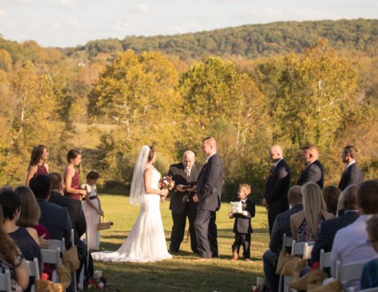 Wedding ceremony in front of rolling hills with green trees with bride in white dress and groom in black suit