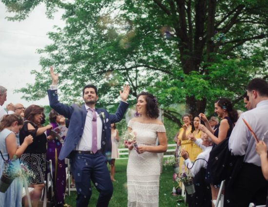 Wedding ceremony in front of large tree with green leaves with bride in white dress and groom in dark purple suit walking down the aisle