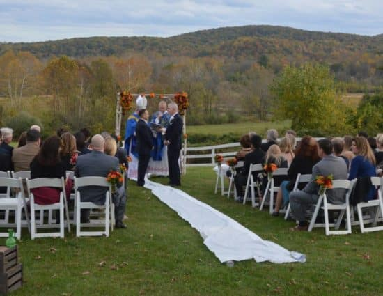 Wedding ceremony with rolling hills in the background and two grooms with dark blue suits