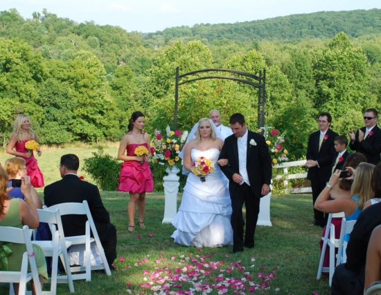 Wedding ceremony with rolling hills filled with green trees in the background with bride in white dress and groom in black suit