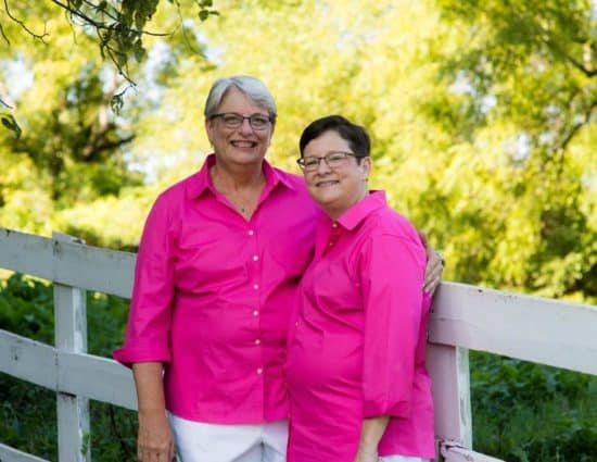 Two brides with pink shirts and white pants standing by white fence