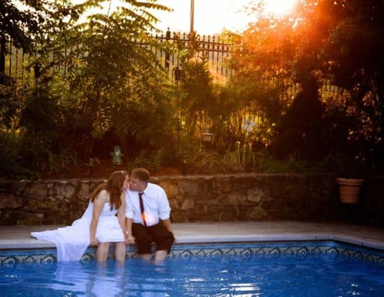 Bride with white dress and groom with white shirt and black pants sitting by pool with legs in the water