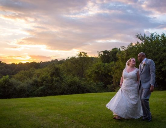 Bride with white dress and groom with gray suit standing on green grass with the sun setting behind them