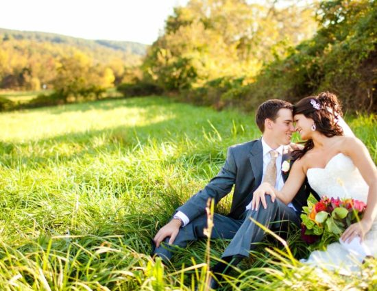 Bride with white dress and groom with gray suit sitting in field of green grass