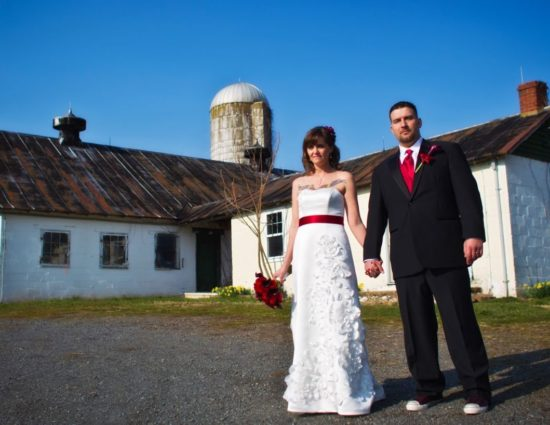 Bride with white dress and groom with black suit standing in front of old barn and silo