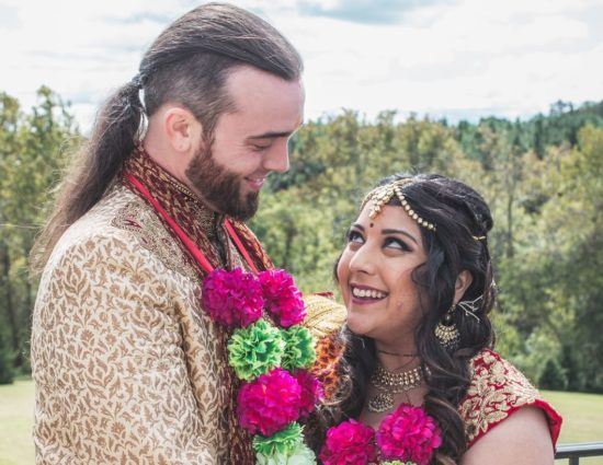 Bride and groom with traditional Indian wedding attire looking at each other