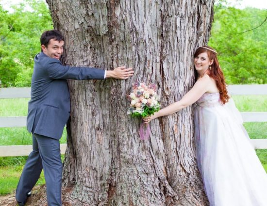 Bride with white dress and groom with gray suit hugging large tree