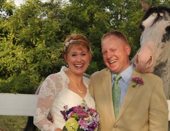 Bride with white dress and groom with tan suit standing by white and black horse with head on groom's shoulder