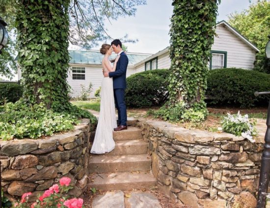 Bride with white dress and groom with navy suit standing on steps in front of white cottage