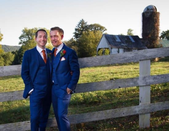 Two grooms in blue suits standing by old fence with old barn and silo in background