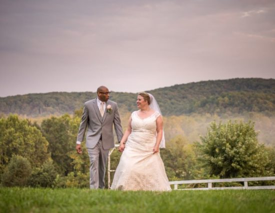 Bride with white dress and groom with gray suit standing near white fence with rolling hills in the background