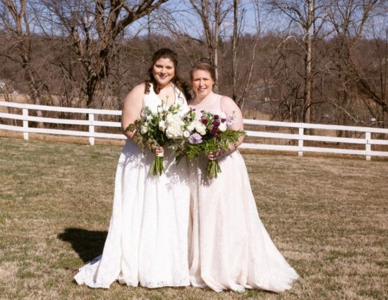 Two brides with white dresses standing in grass with white fence behind them