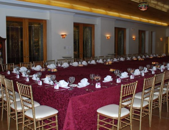 Large room with concrete flooring set up for wedding reception with burgundy tablecloths and white napkins