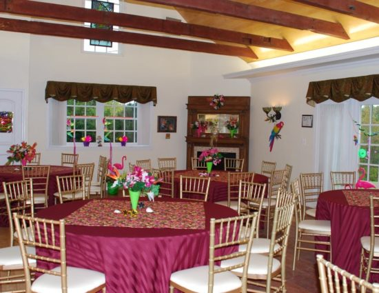 Large room with hardwood flooring set up for wedding reception with burgundy tablecloths