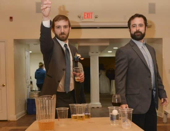 Two men with gray suits playing beer pong