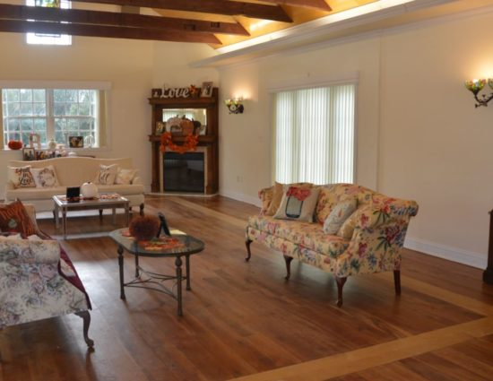 Large room with hardwood flooring, dark wood China hutch, upholstered couches, coffee tables, and fireplace in the corner