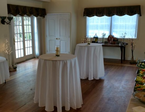 Large room set up with cocktail and round tables with white tablecloths and a table with appetizers