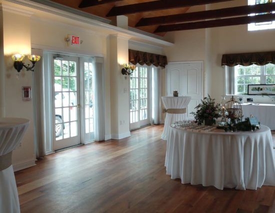 Large room with hardwood flooring set up for a cocktail reception with tables with white tablecloths