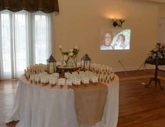 Large room with hardwood flooring, large round table with white tablecloth and wedding party favors, and slideshow in the background