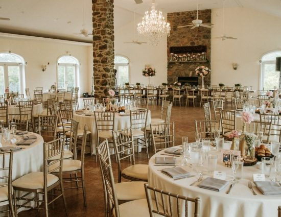 Large room set up for a wedding reception with cream tablecloths and gray napkins