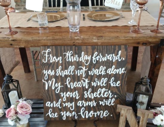 Old wooden table set up for bride and groom, a wooden panel with a saying in white lettering, and white and pink flowers in vases