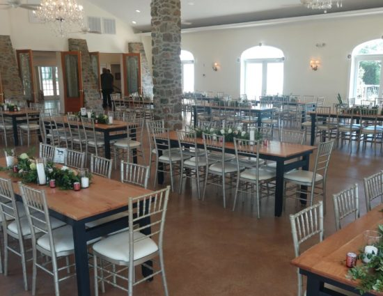 Large room set up for a wedding reception with flower garlands on all tables